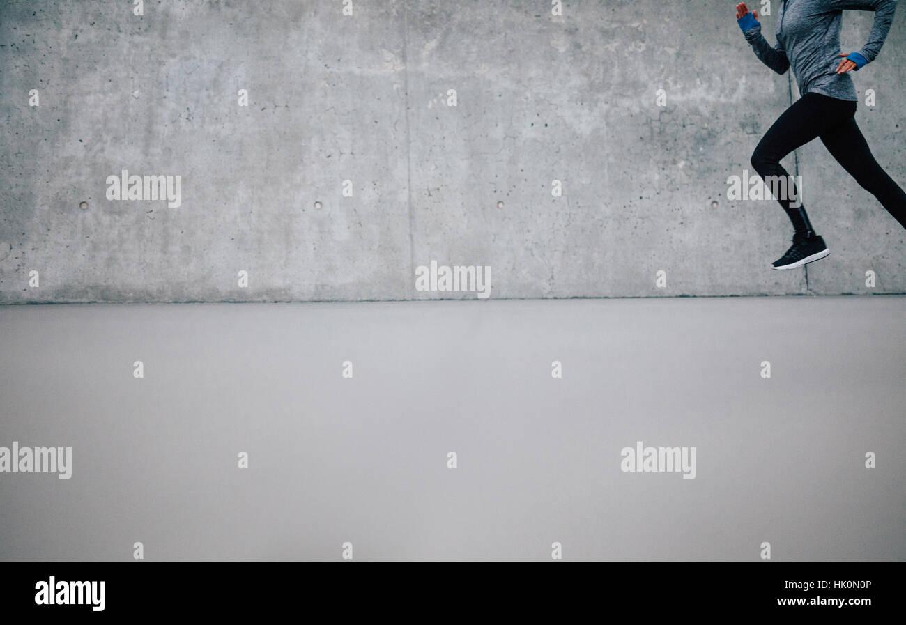 Läufer-Athlet läuft auf grauem Hintergrund. Fitness-Frau mit vielen textfreiraum Joggen. Stockfoto