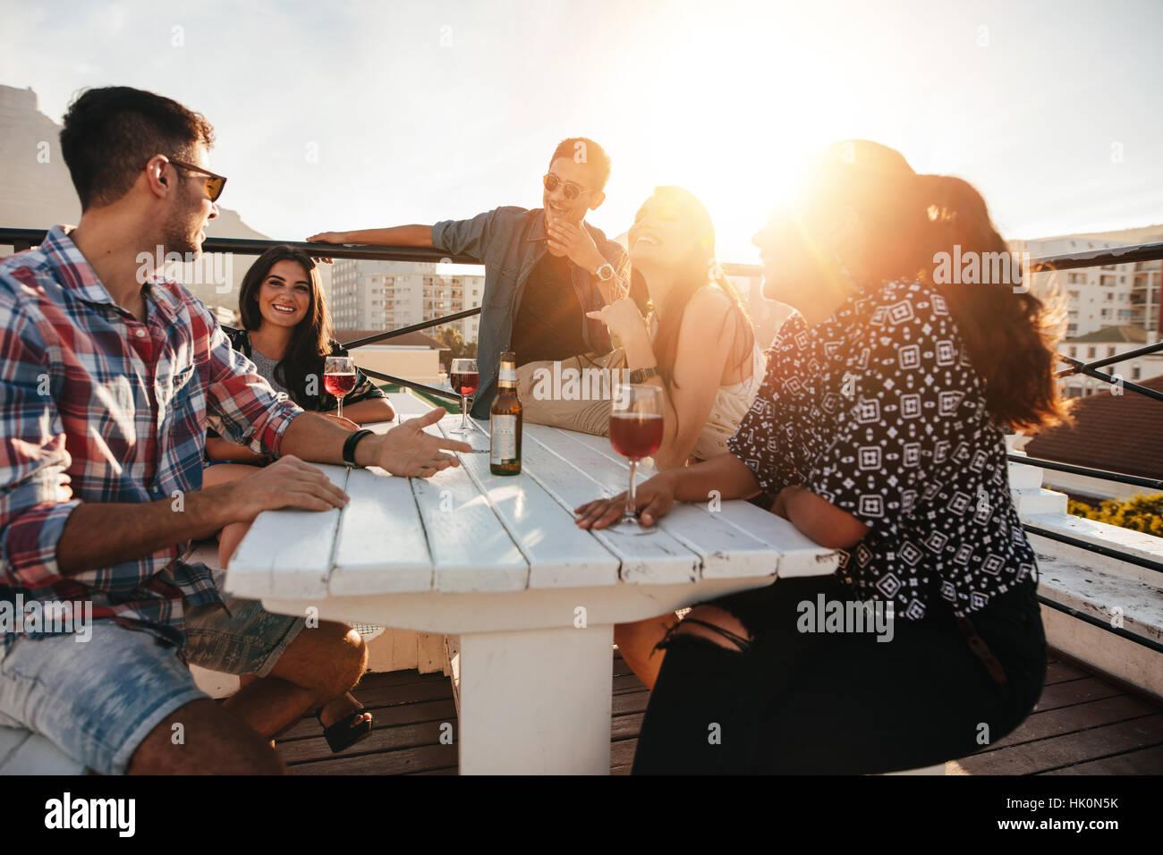 Gruppe von jungen Leuten an einem Tisch mit Getränken. Junge Männer und Frauen, die auf dem Dach Abend feiern. Stockfoto