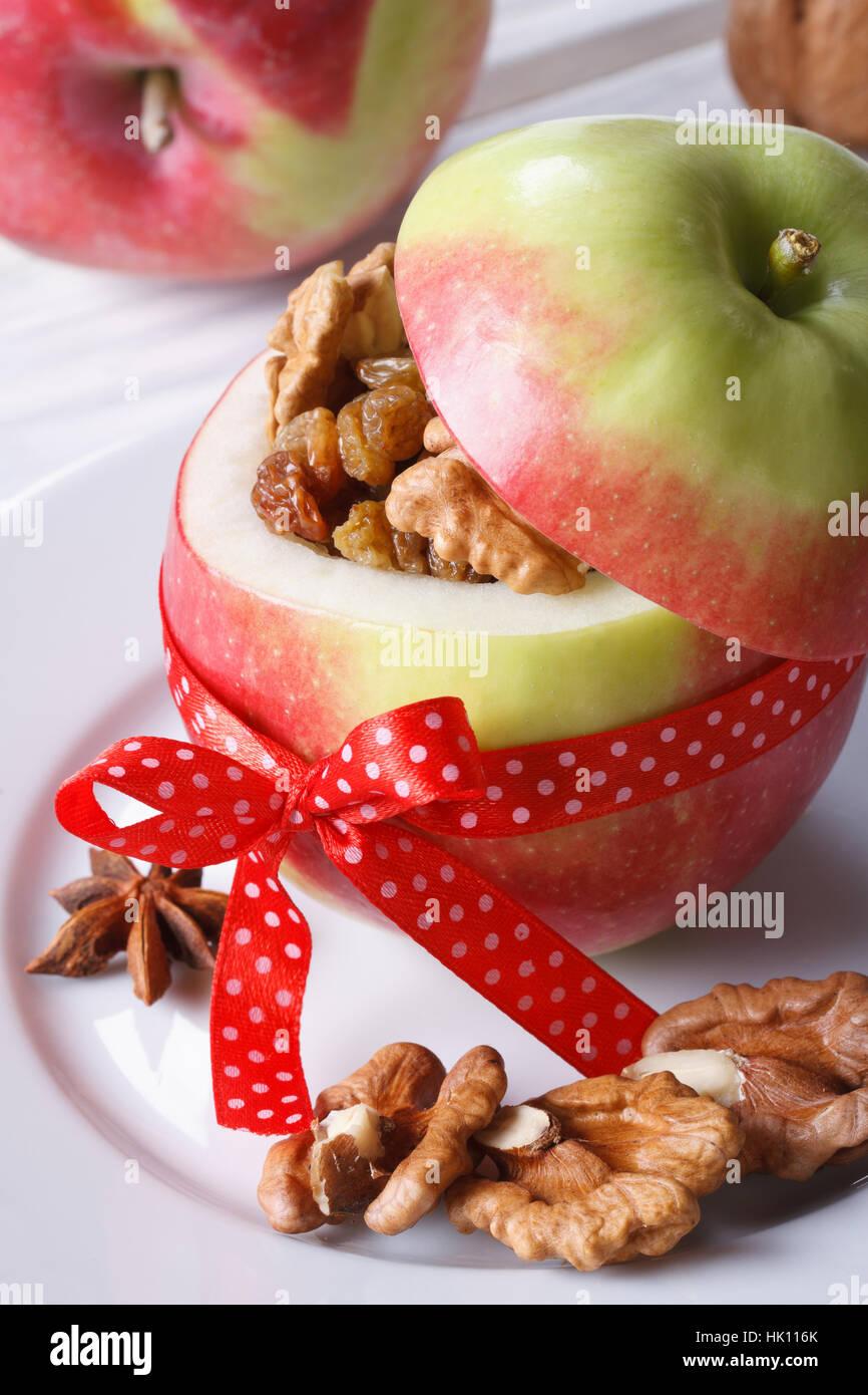 festlicher rote Apfel gefüllt mit Nüssen und Rosinen auf einem weißen Teller auf dem Tisch hautnah Stockbild