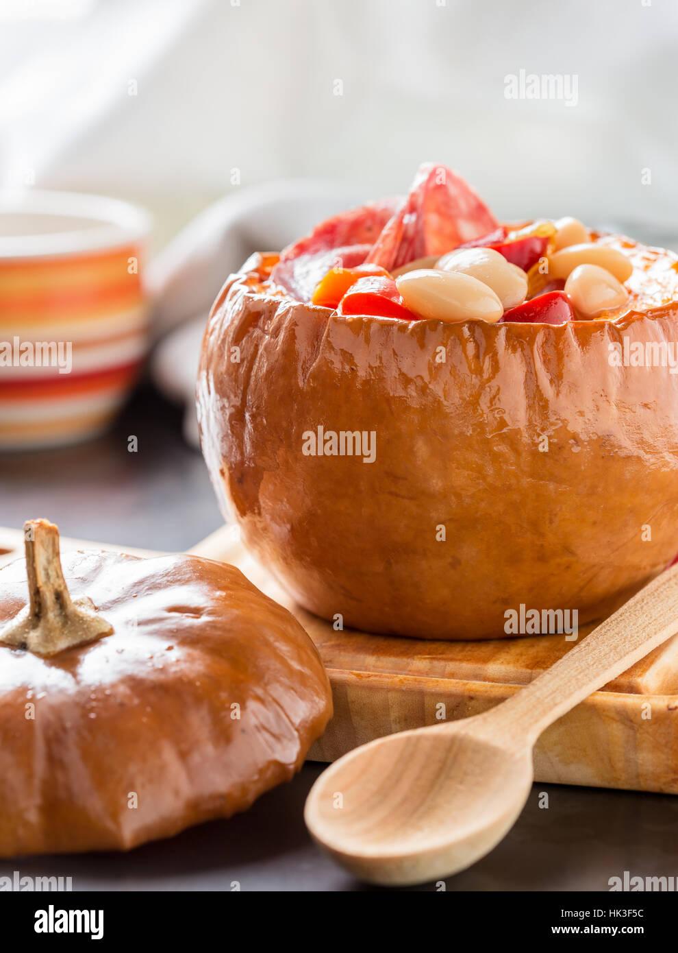 Weiße Bohnen und Paprika-Gemüse-Eintopf in Kürbis Schüsseln serviert auf Holzbrett Stockbild