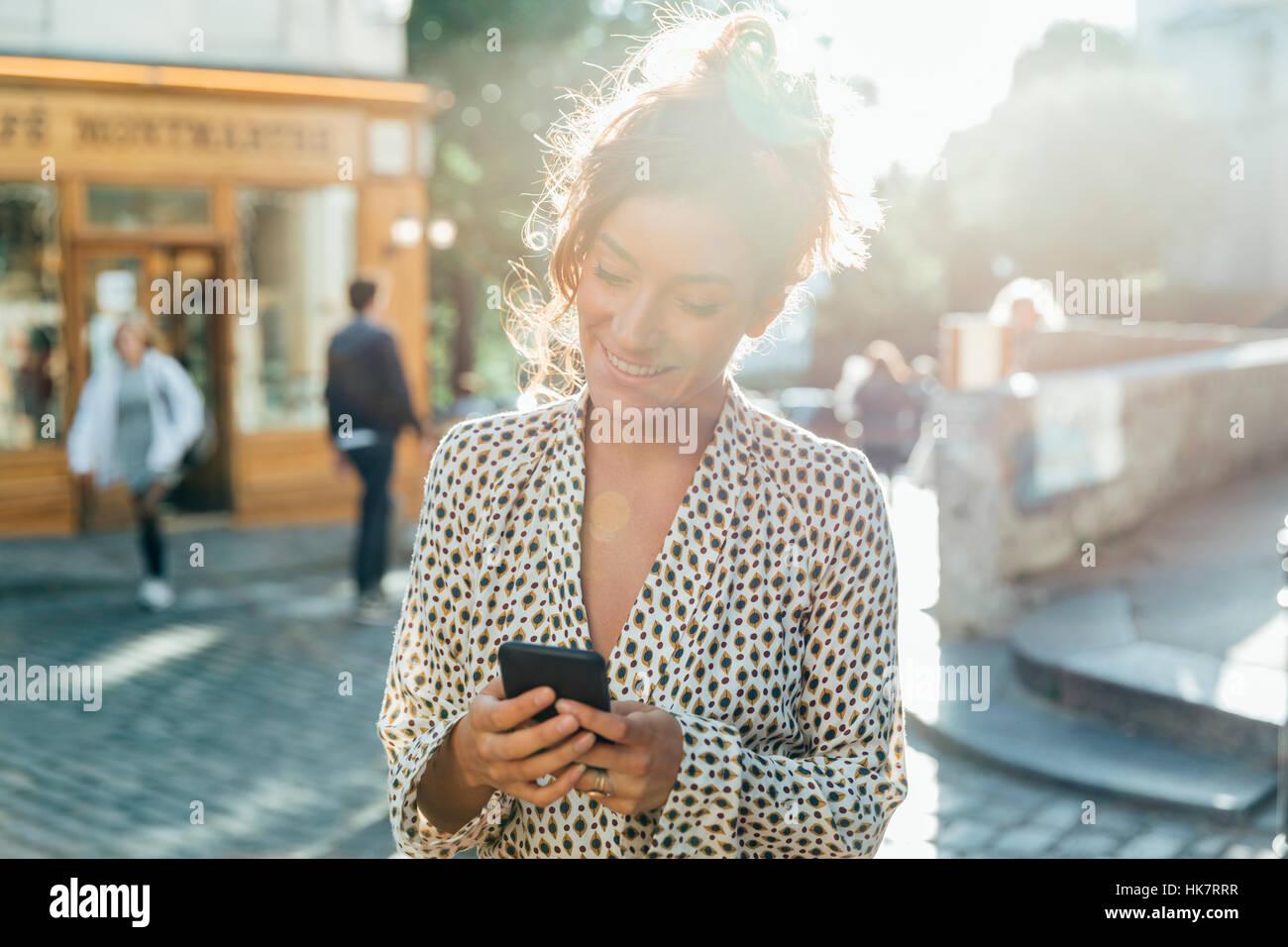 Paris, attraktive Frau Viertel Montmartre zu Besuch und die Nutzung eines smart phone Stockbild