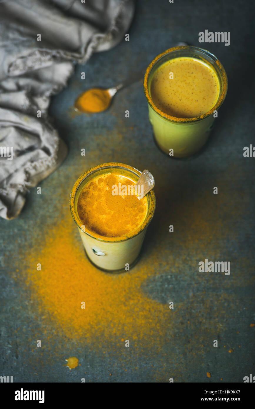 Goldene Milch mit Kurkuma-Pulver in Gläsern über dunkle Grunge Hintergrund, Textfreiraum. Gesundheit oder Stockbild