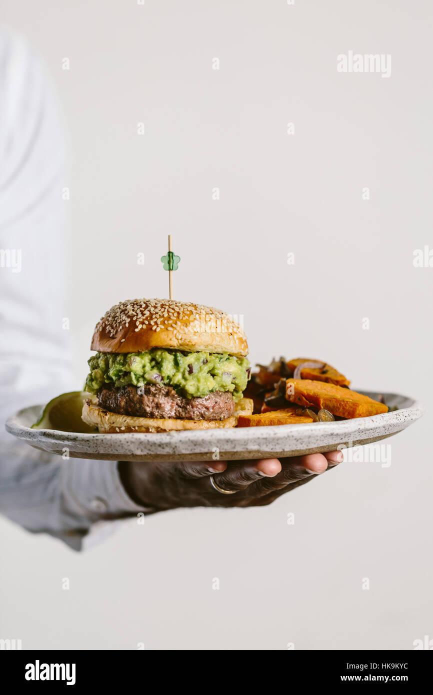 Ein Mann wird aus der Vorderansicht halten Sie einen Teller mit Guacamole Burger und Süßkartoffel Pommes Stockbild