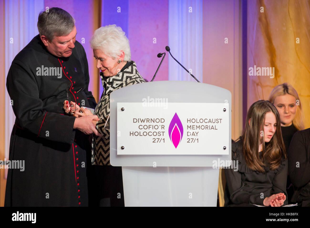 Cardiff, Wales, Großbritannien. 27. Januar 2017.  Holocaust-Überlebende Eva Clarke wird unterstützt Stockbild