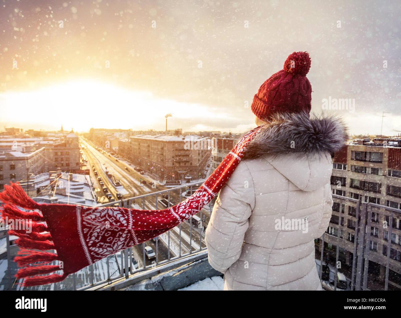 Frau in Weihnachtshut und Roter Schal auf dem Dach bei Schnee fallen in Sankt Petersburg, Russland Stockbild