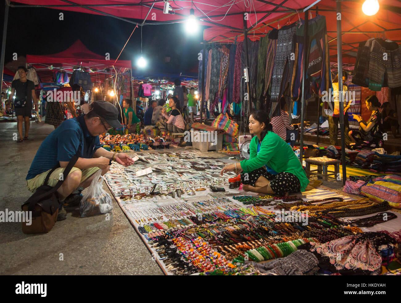LUANG PRABANG, LAOS - 15. Mai 2015: Ein Tourist sucht nach Souvenir in Luang Prabang Nachtmarkt, einem erstklassigen Stockbild