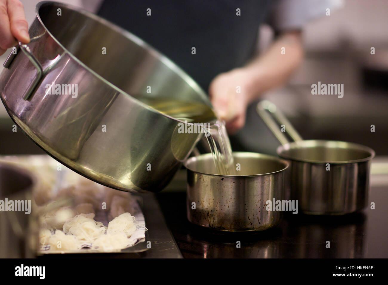 Hände gießen Öl in Küchengerät. Töpfe und Pfannen, Container, gießen, Essen trinken. Stockbild