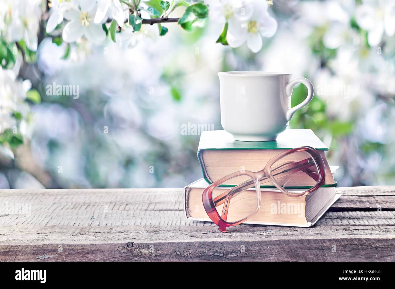 hei en kaffee oder tee kakao schokolade tasse auf buch und brille im freien im fr hling oder. Black Bedroom Furniture Sets. Home Design Ideas