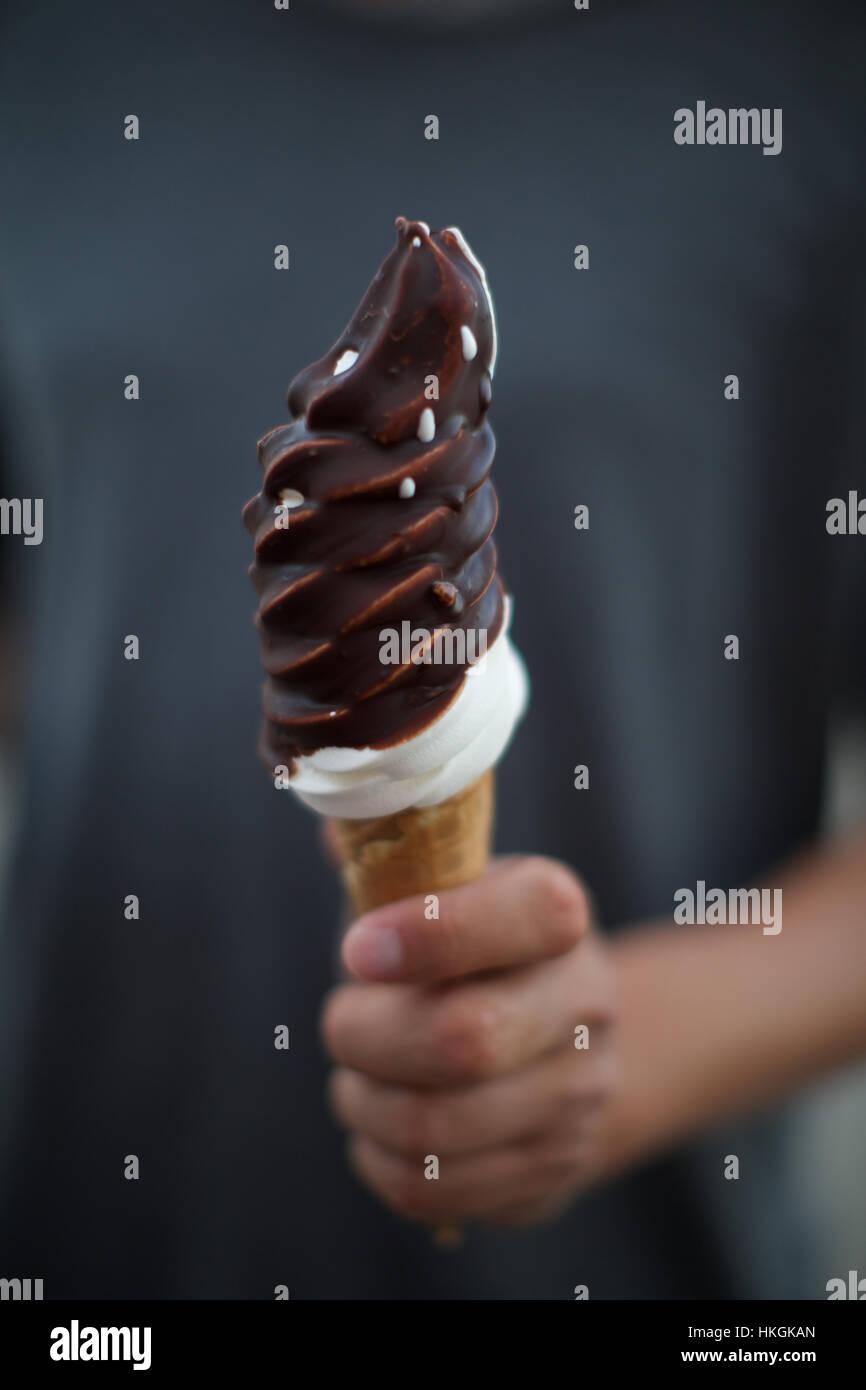 Hand hält Softice Kegel mit Schokolade bestreuen. Süßigkeiten, Eis, ungesund, Essen. Stockbild