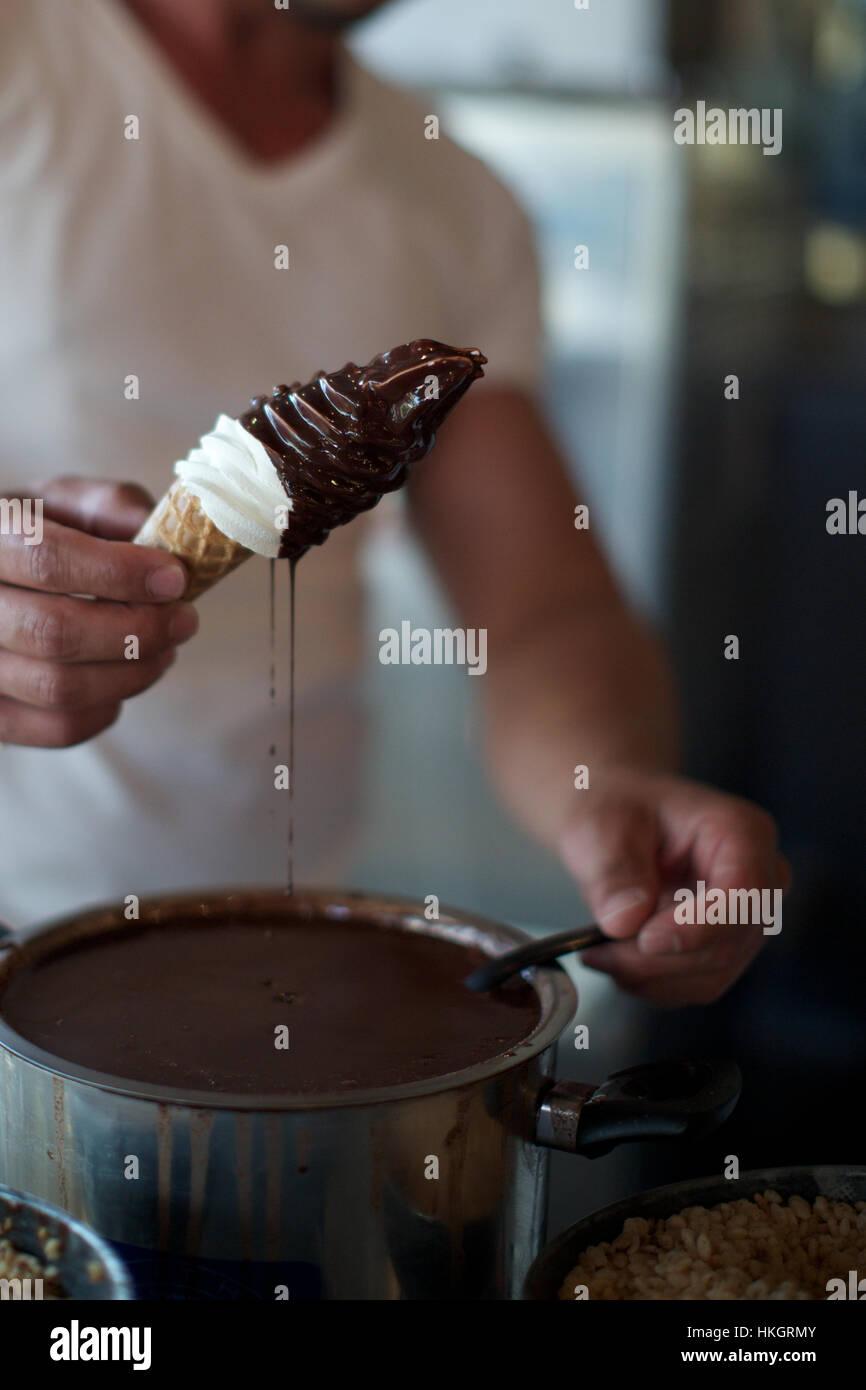 Mann hält Softice Kegel mit Schokolade zu verschütten. Container, Eis, ungesund, Essen. Stockbild