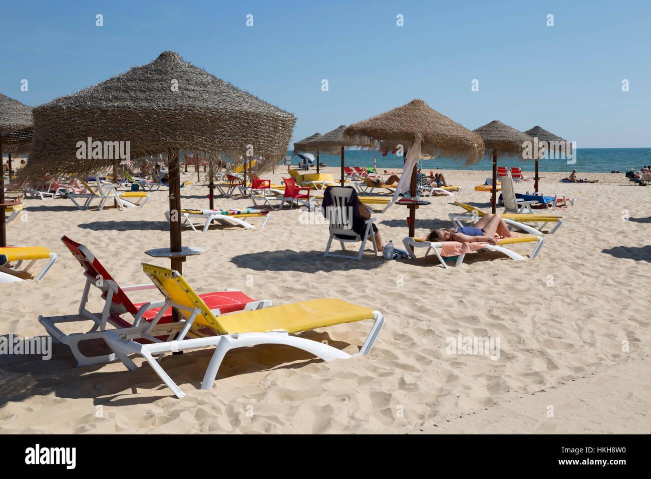 Sonne sand, Liegestühle und Sonnenschirme am weißen Strand, Monte Gordo, Algarve, Portugal, Europa Stockbild