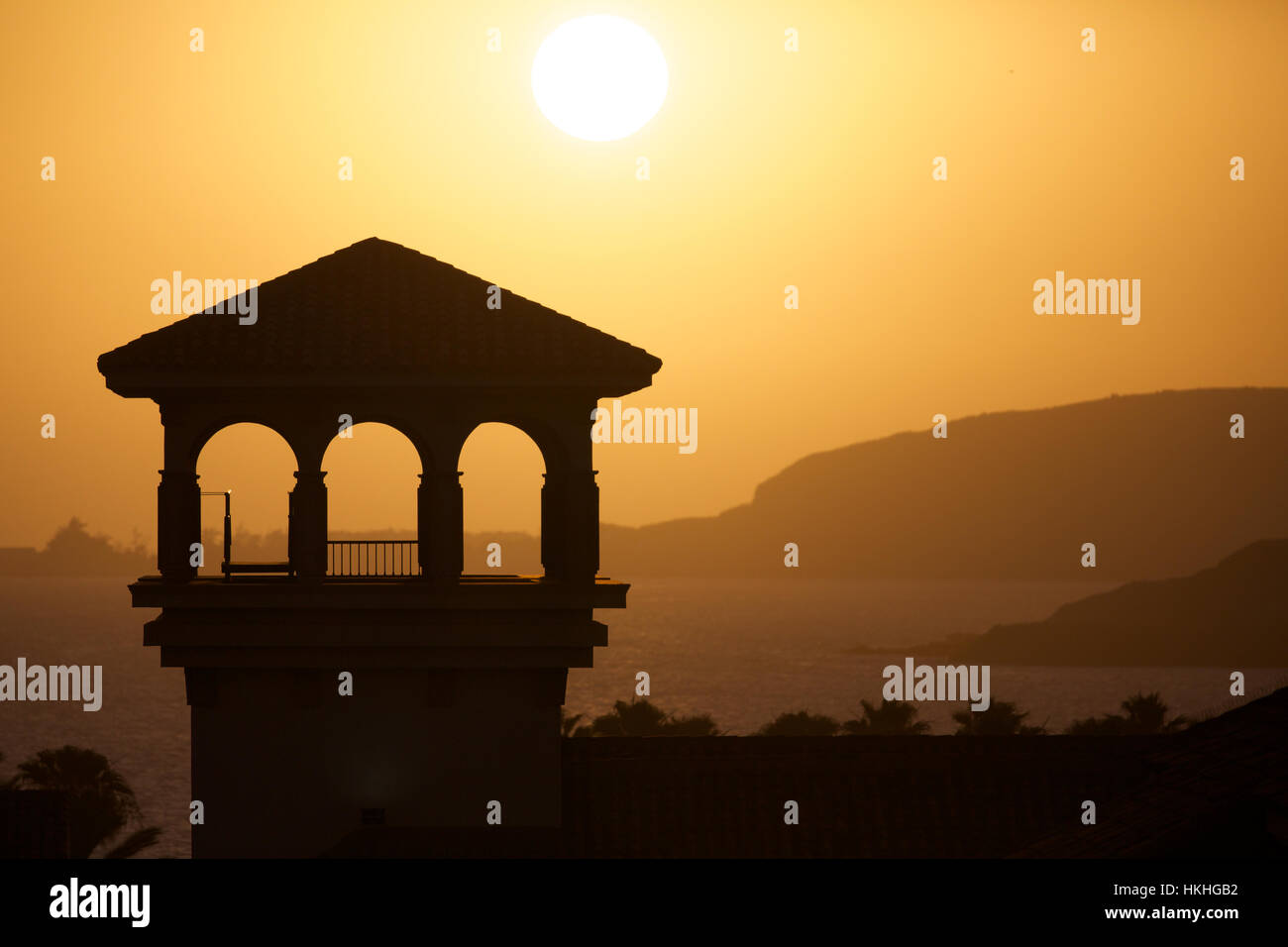 Silhouette der gebauten Struktur während des Sonnenuntergangs. Fluss, Dämmerung, Naturidylle. Stockbild