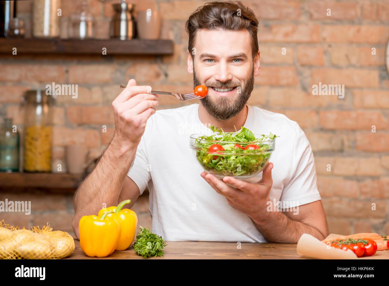 Mann isst Salat Stockbild