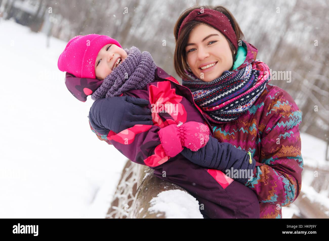 Brünette umarmen Tochter im winter Stockbild