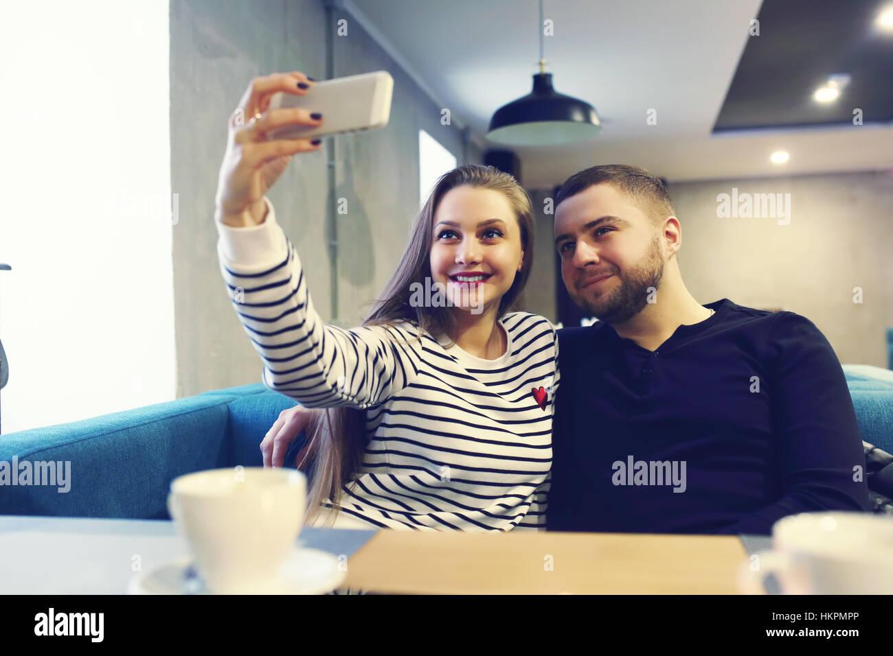 glückliches junges Paar mit Smartphone unter Selfie im Café im Einkaufszentrum. Verkauf, Einkaufen, Konsum, Stockbild