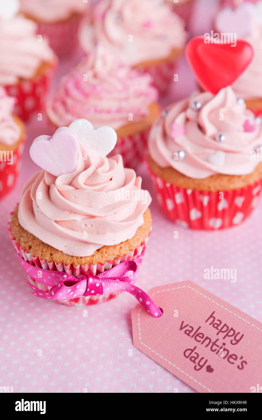 """Rosa Valentine Cupcakes mit den Worten """"Happy Valentine's Day"""" auf einem Schild. Stockbild"""