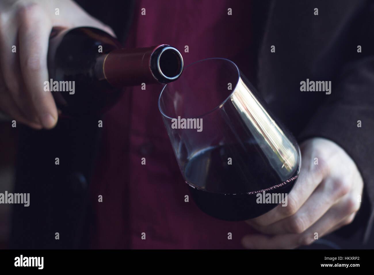Horizontale Nahaufnahme von kaukasischen Mann im schwarzen Anzug und Hemd strömenden Rotwein in ein hohes Glas Stockbild