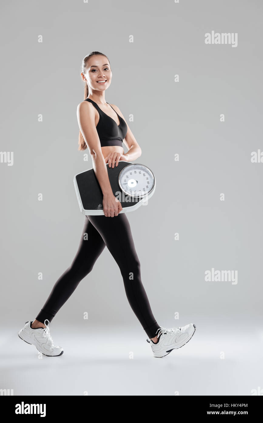 Glücklich niedliche junge Sportlerin zu Fuß und Abhaltung Waage über grauer Hintergrund Stockfoto