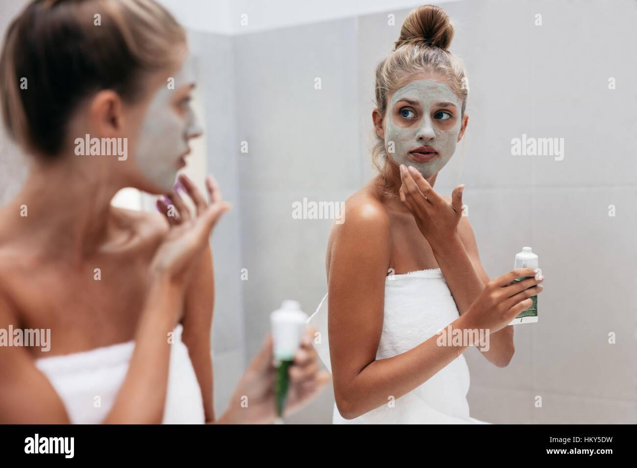Junge Frau Auftragen der Maske Creme auf Gesicht im Badezimmer. Weibchen in Beauty-Behandlung auf ihre Gesichtshaut Stockbild