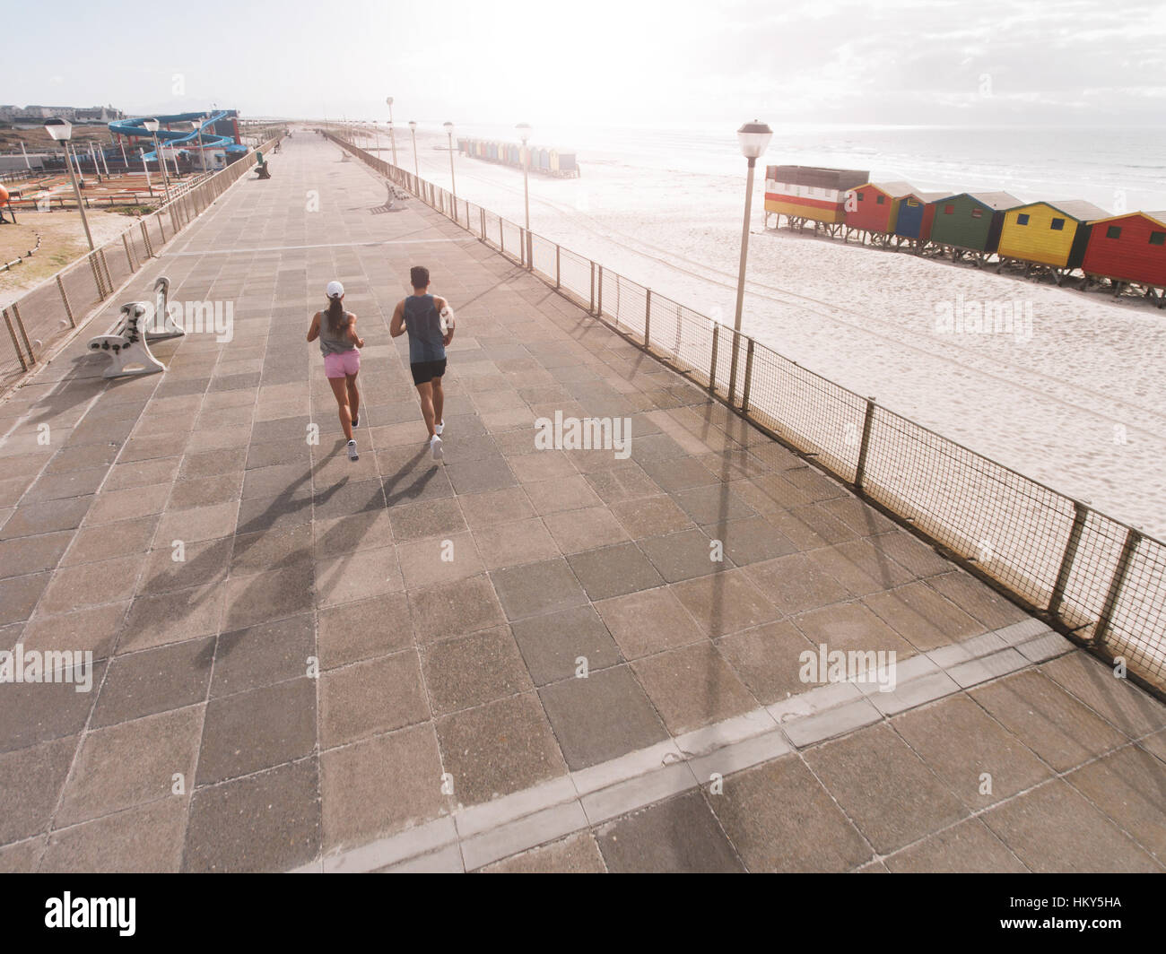 Hintere Ansicht Schuss des jungen Paares am Morgen laufen an Strandpromenade. Junger Mann und Frau auf der Straße Stockbild