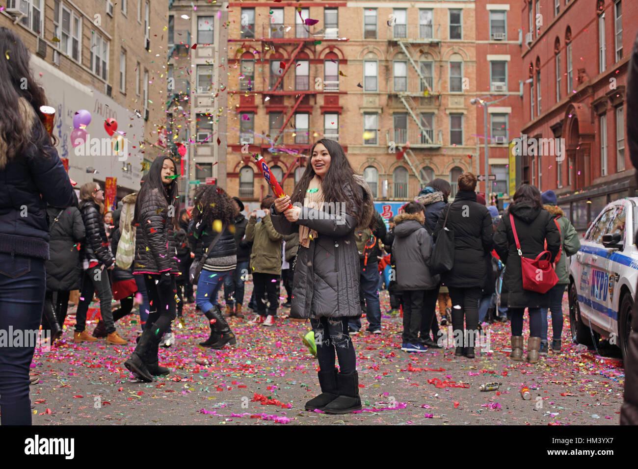 Mädchen-Shootings aus Riesen-Party Popper, Konfetti und Glitzer Wurf eine NYC Chinatown Straße am ersten Tag des Stockfoto
