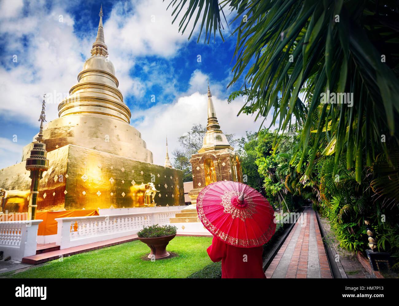 Frau Tourist mit roten traditionelle Thai Regenschirm in der Nähe von goldenen Stupa im Tempel Wat Phra Singh in Chiang Mai, Thailand Stockfoto