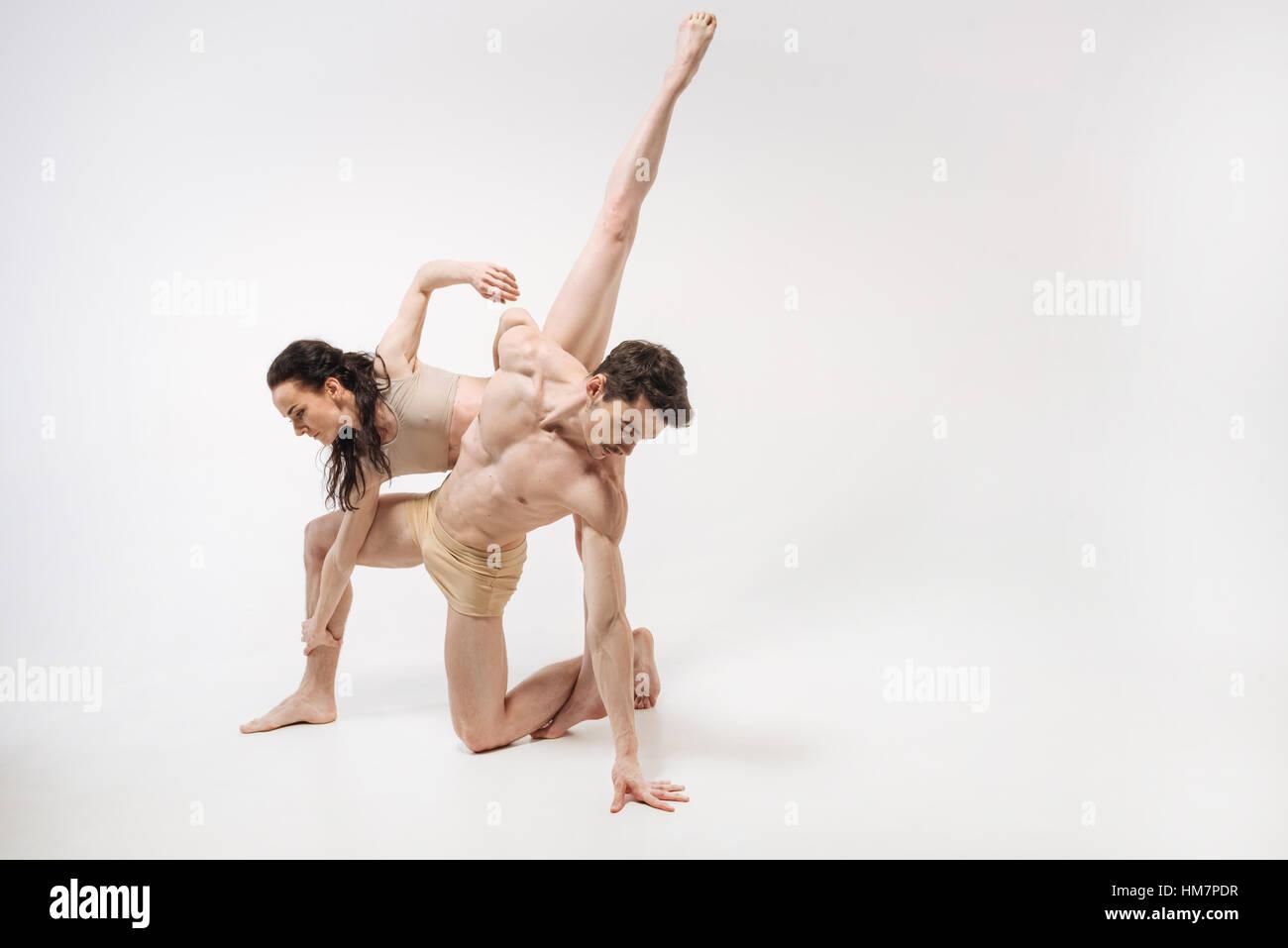 Elegante junge Ballett-Tänzer im weißen farbigen Studio durchführen Stockbild