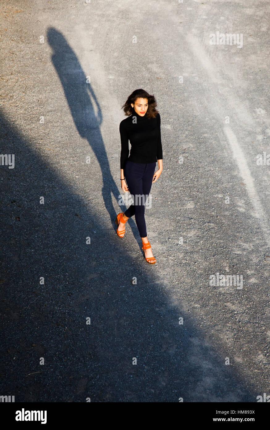 Porträt der selbstbewusste junge Erwachsene Frau in schwarzer Kleidung und Orange Schuhe zu Fuß während Stockbild
