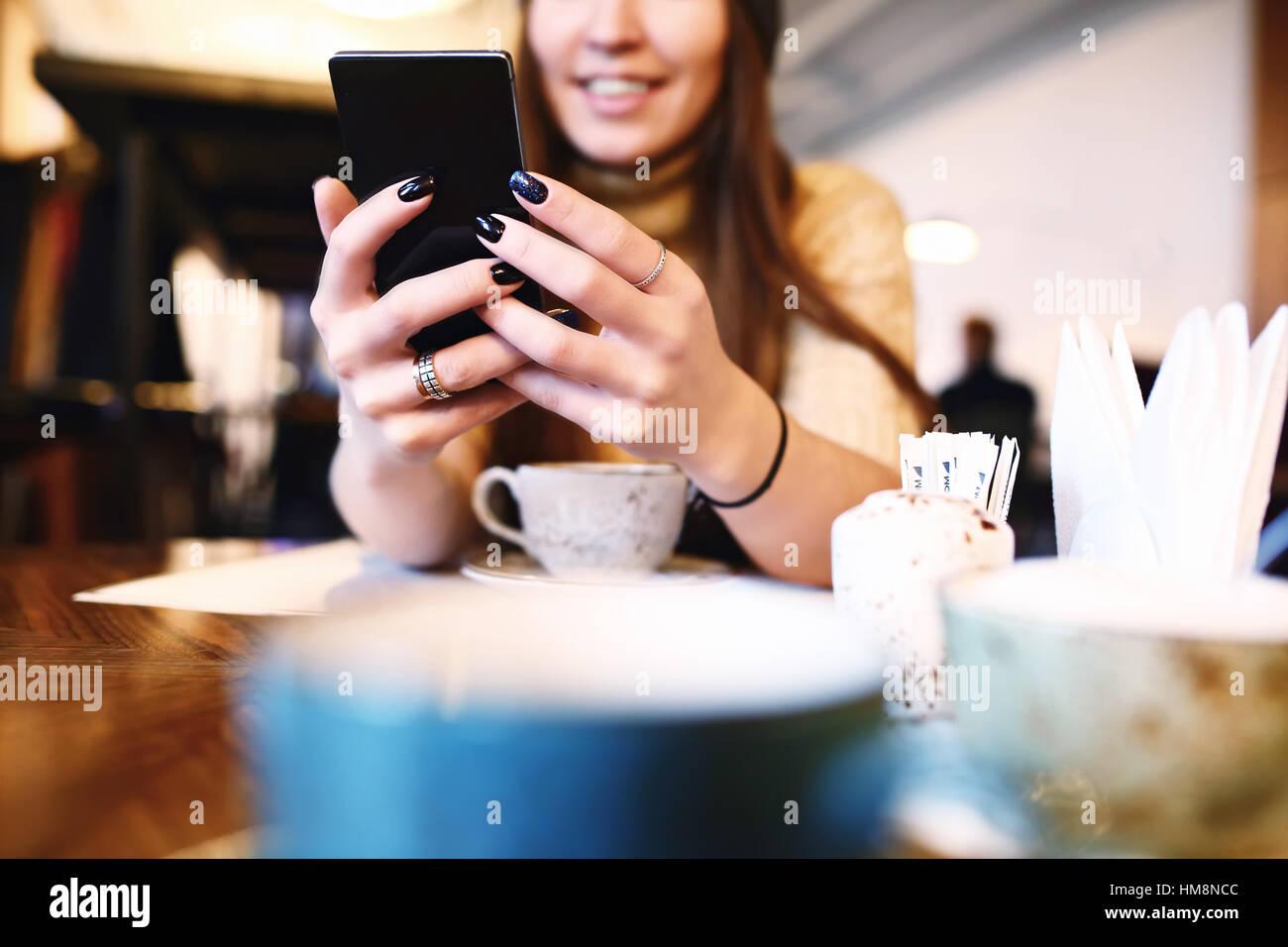 Frau Textmitteilung auf smart Phone in einem Café zu schreiben. Bild junge Frau sitzt an einem Tisch mit einem Stockbild