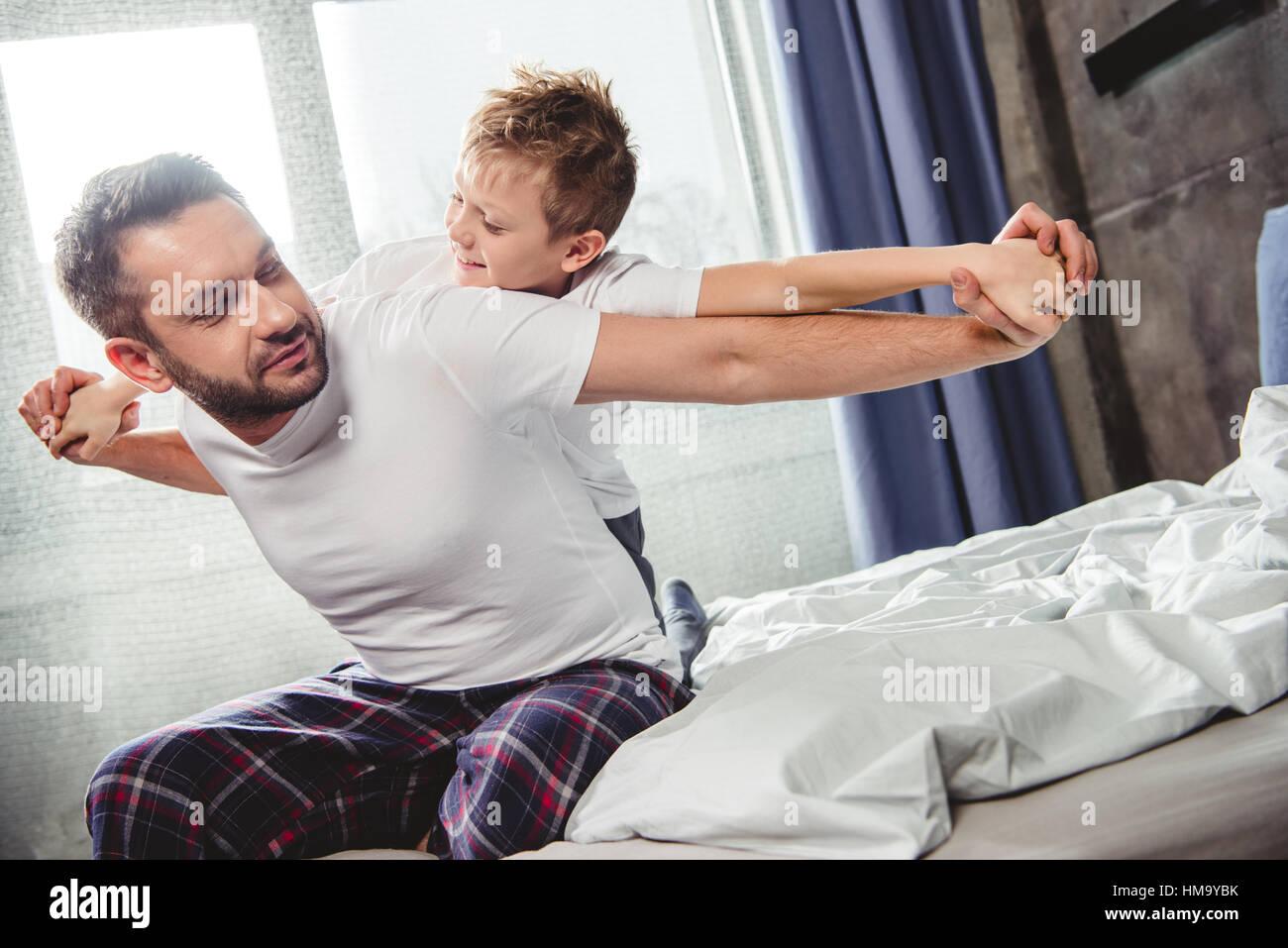 Glücklicher Vater und Sohn im Bett Stockbild