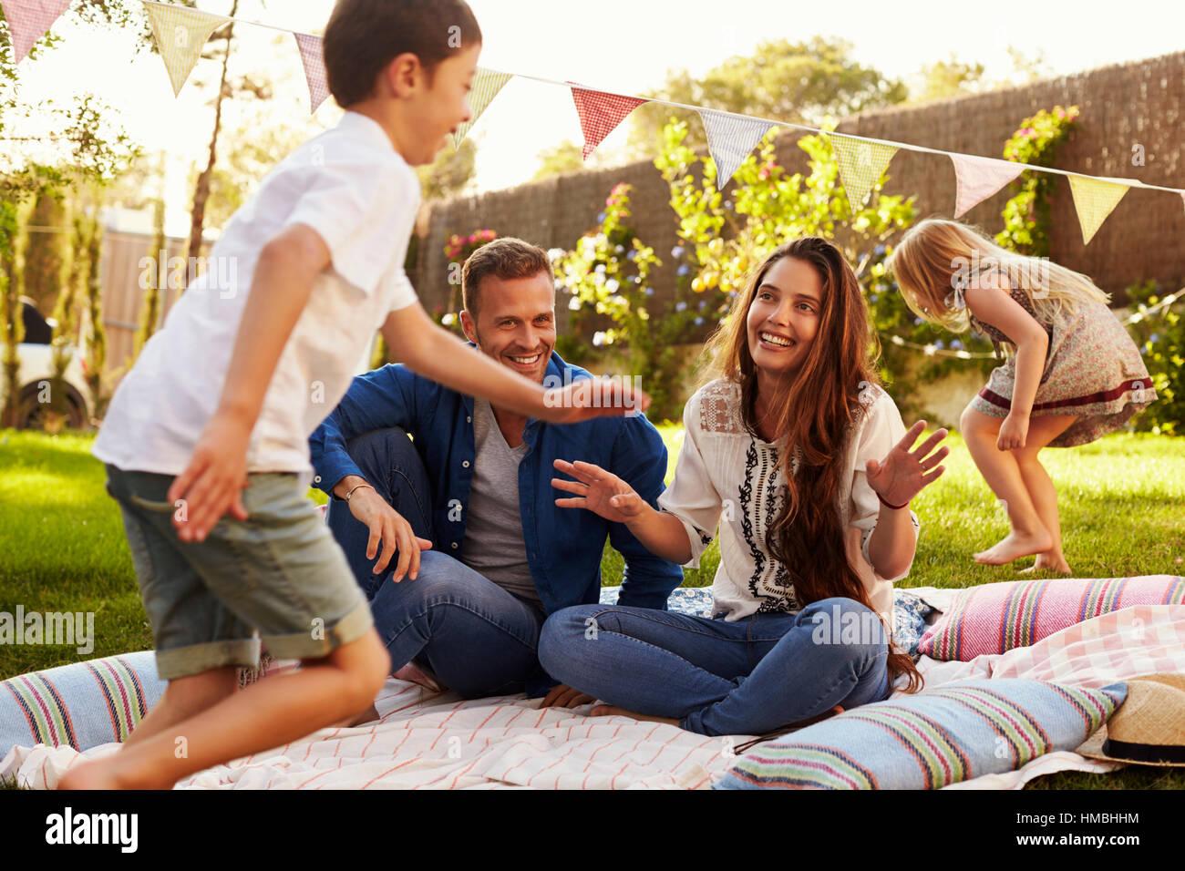 Eltern spielen mit Kindern auf Decke im Garten Stockbild