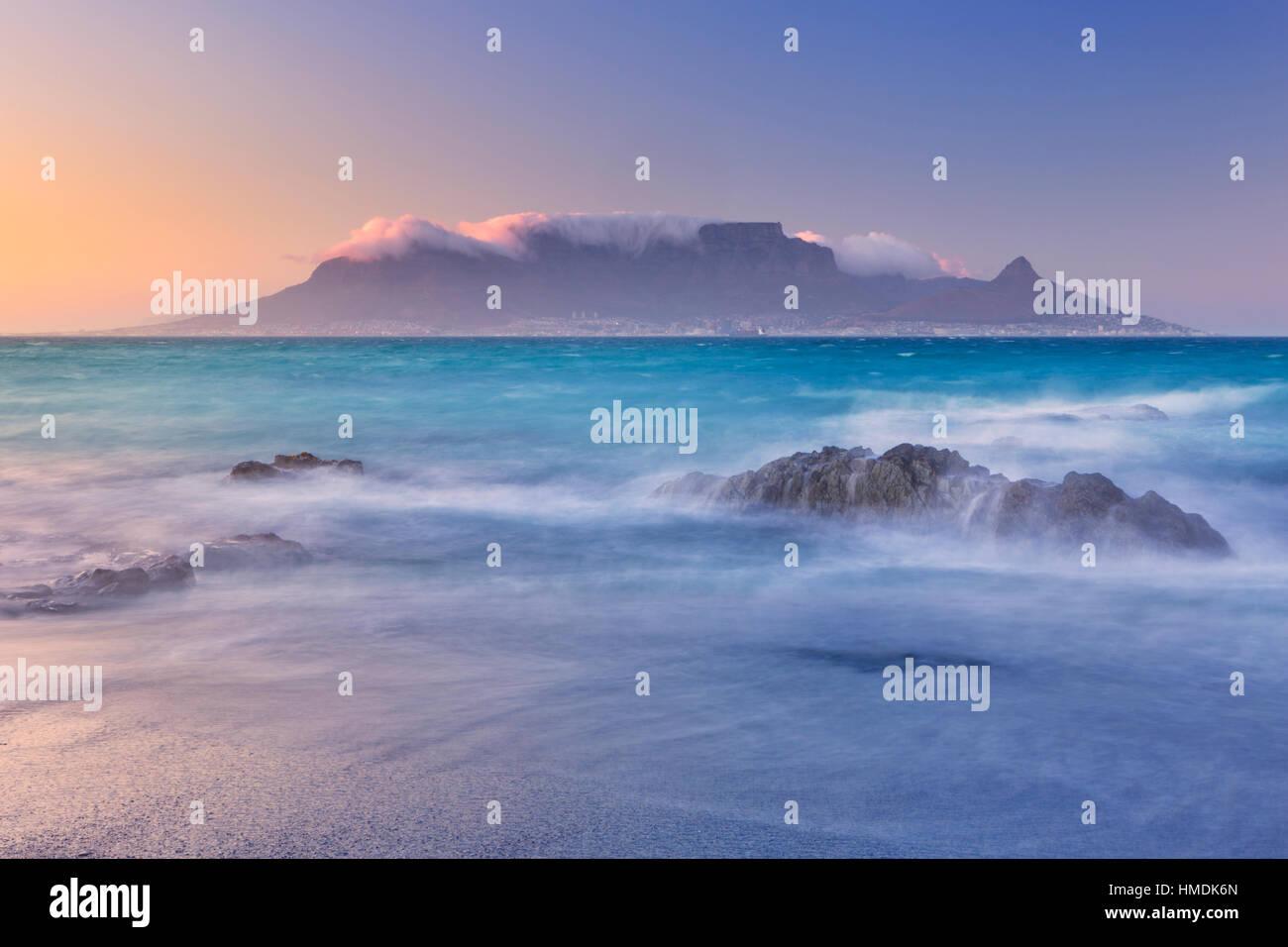 Sonnenaufgang über dem Tafelberg und Kapstadt vom Strand Bloubergstrand. Stockbild
