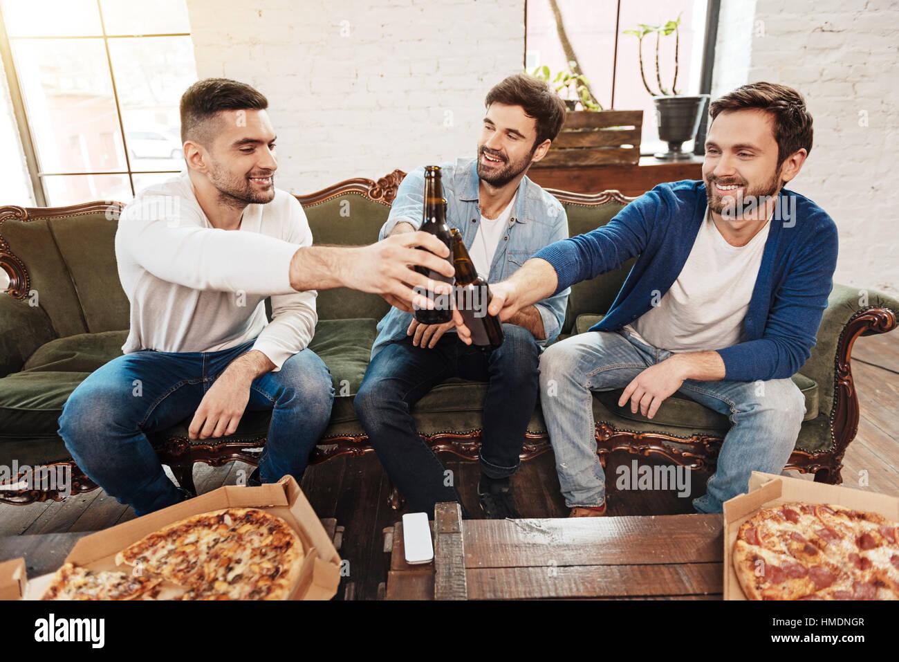 Positive fröhliche Männer heben Bierflaschen für toast Stockbild