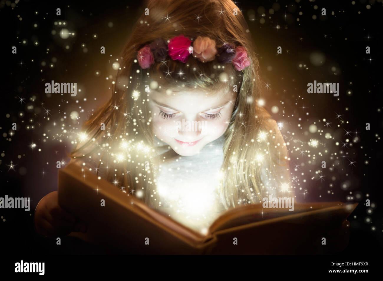 Wunderschönes kleines Mädchen lesen magisches Buch, Fantasy-Konzept Stockbild