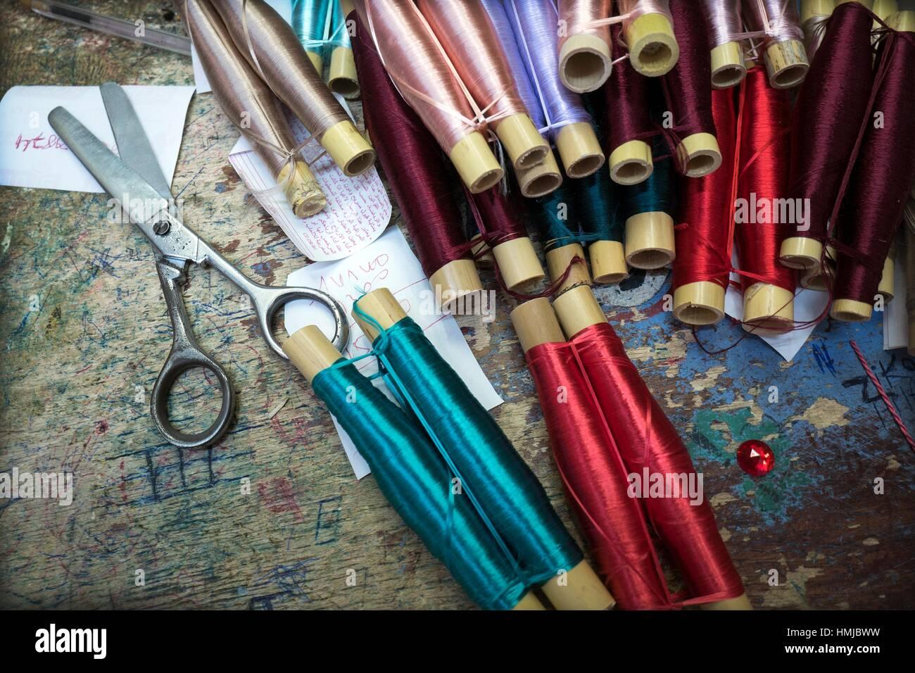 Nahaufnahme von mehreren Rollen von Gewinde in verschiedenen Farben und Schere auf einem rustikalen Tisch. Chaouen, Stockfoto