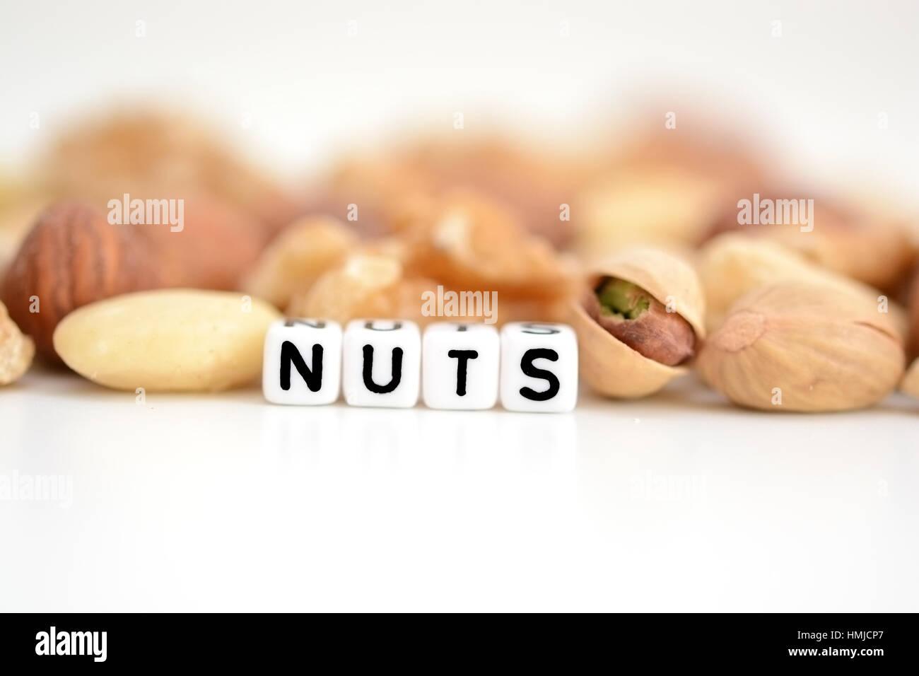 """Rohe Nüsse und das Wort """"Nuts"""" von Fliesen- buchstaben Perlen verteilt auf einem weißen Tisch geschrieben Stockfoto"""