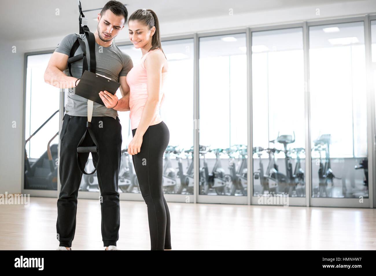 Persönlicher Trainer zeigt Ergebnis der Trainingsplan an seinen weiblichen jungen Klienten mit Aussetzung Seil Stockbild