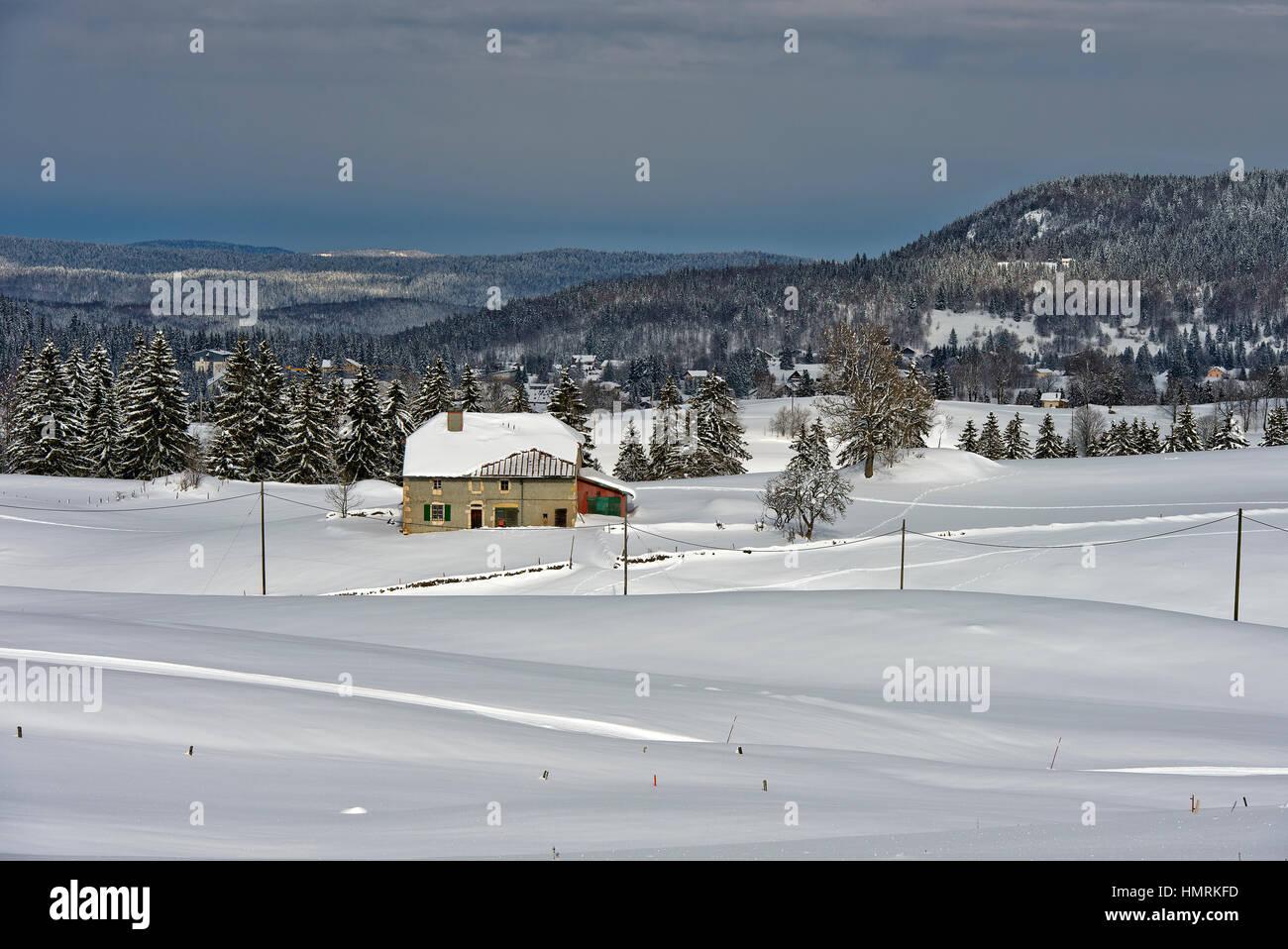 Abgelegenen Bauernhof in der tief verschneiten Landschaft des Schweizer Jura-Gebirges in der Nähe der Ortschaft Stockbild