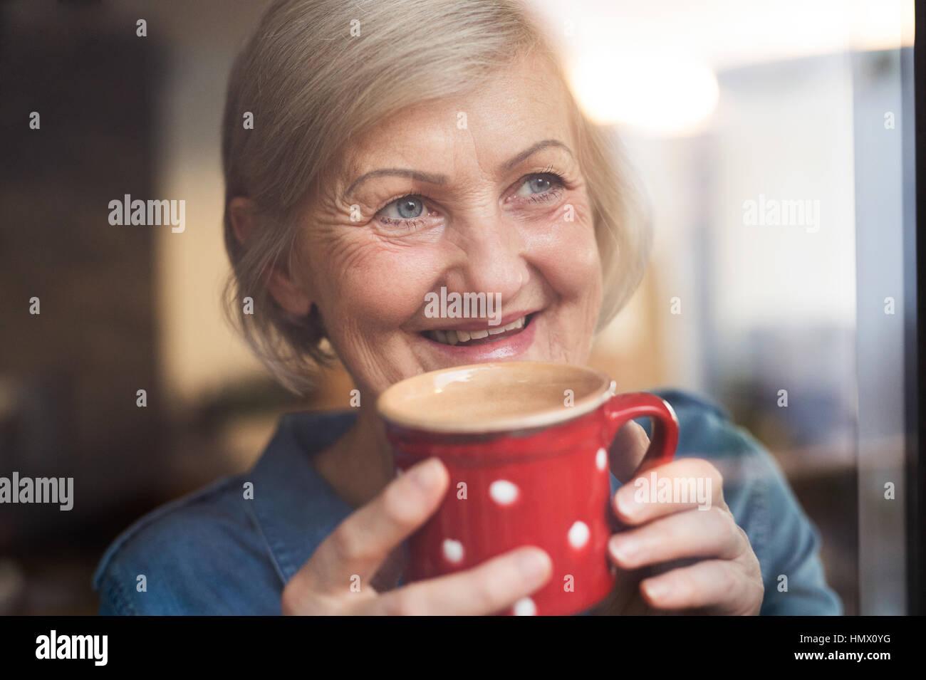Ältere Frau am Fenster hält eine Tasse Kaffee Stockfoto