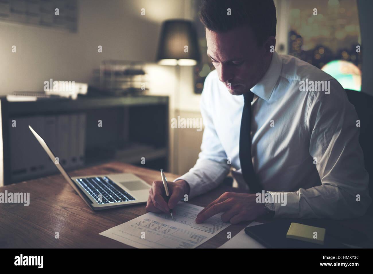Geschäftsmann Arbeiten konzentrierten sich auf Dokumente in der Nacht, Überstunden im Büro Stockbild