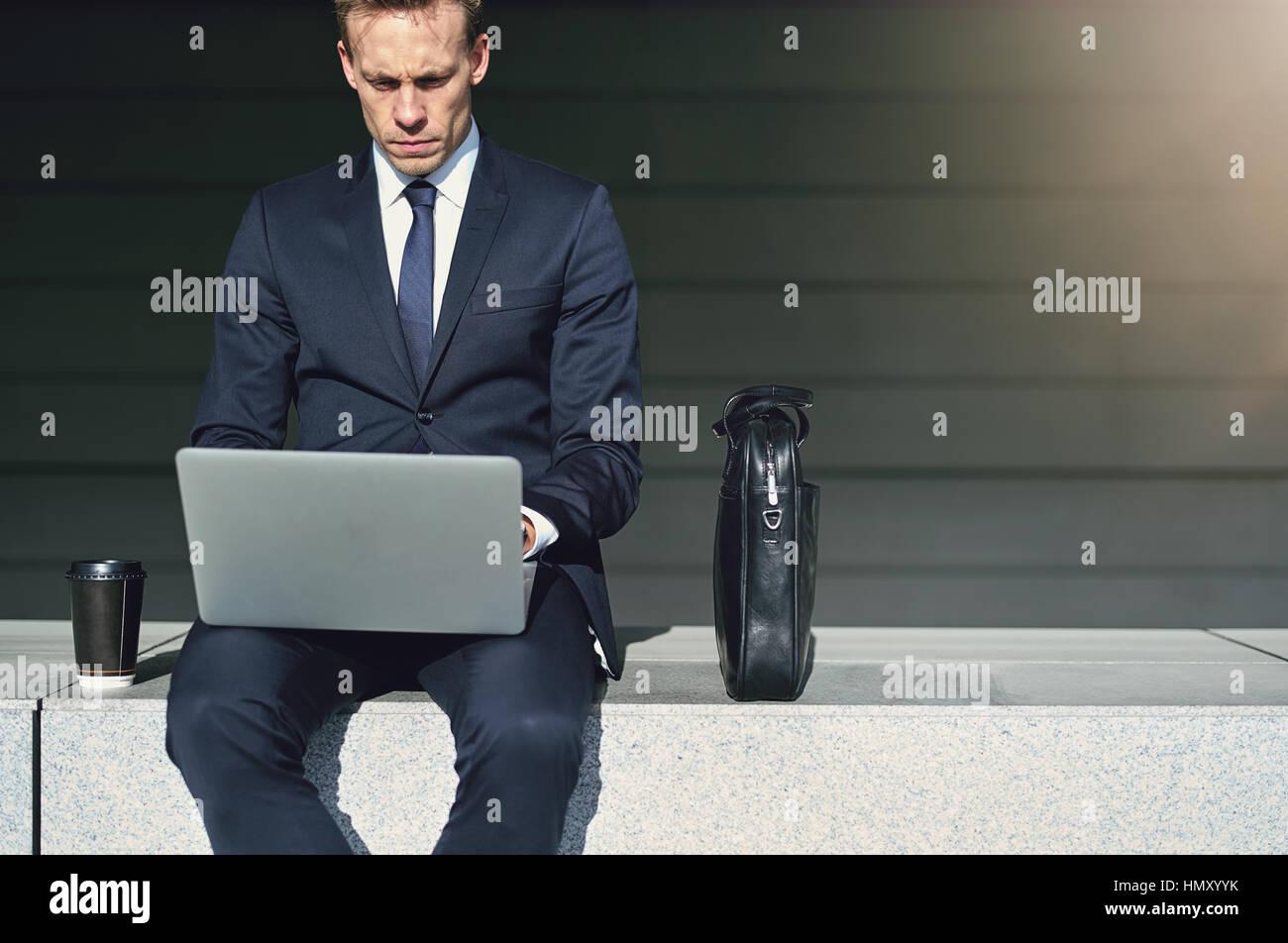 Stilvolle Geschäftsmann während der Arbeit auf seinem notebook Stockbild