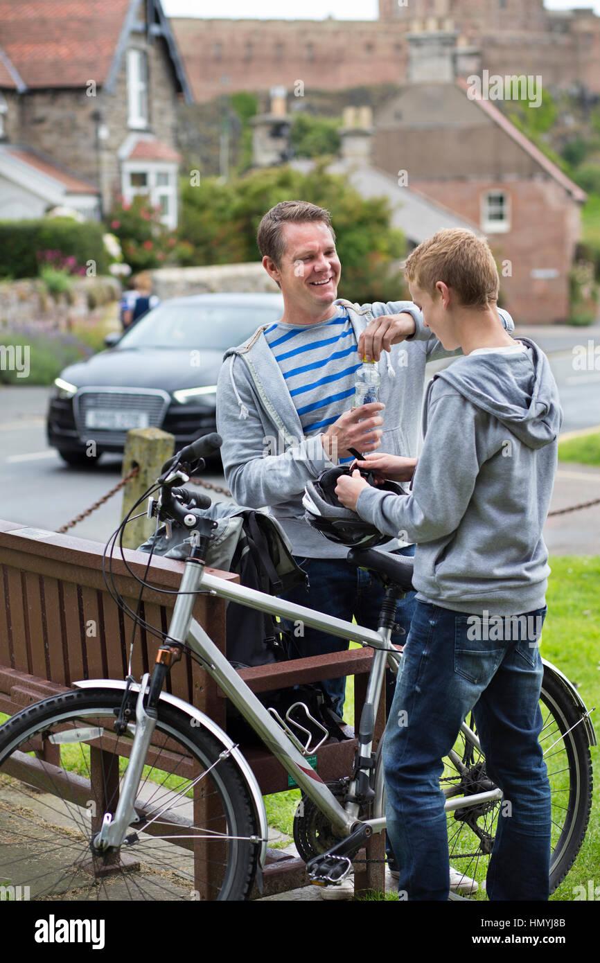 Vater und Sohn in einem Dorf in der Mitte ihrer Radtour zu stoppen, einen Drink zu nehmen. Sie tragen Freizeitkleidung Stockbild