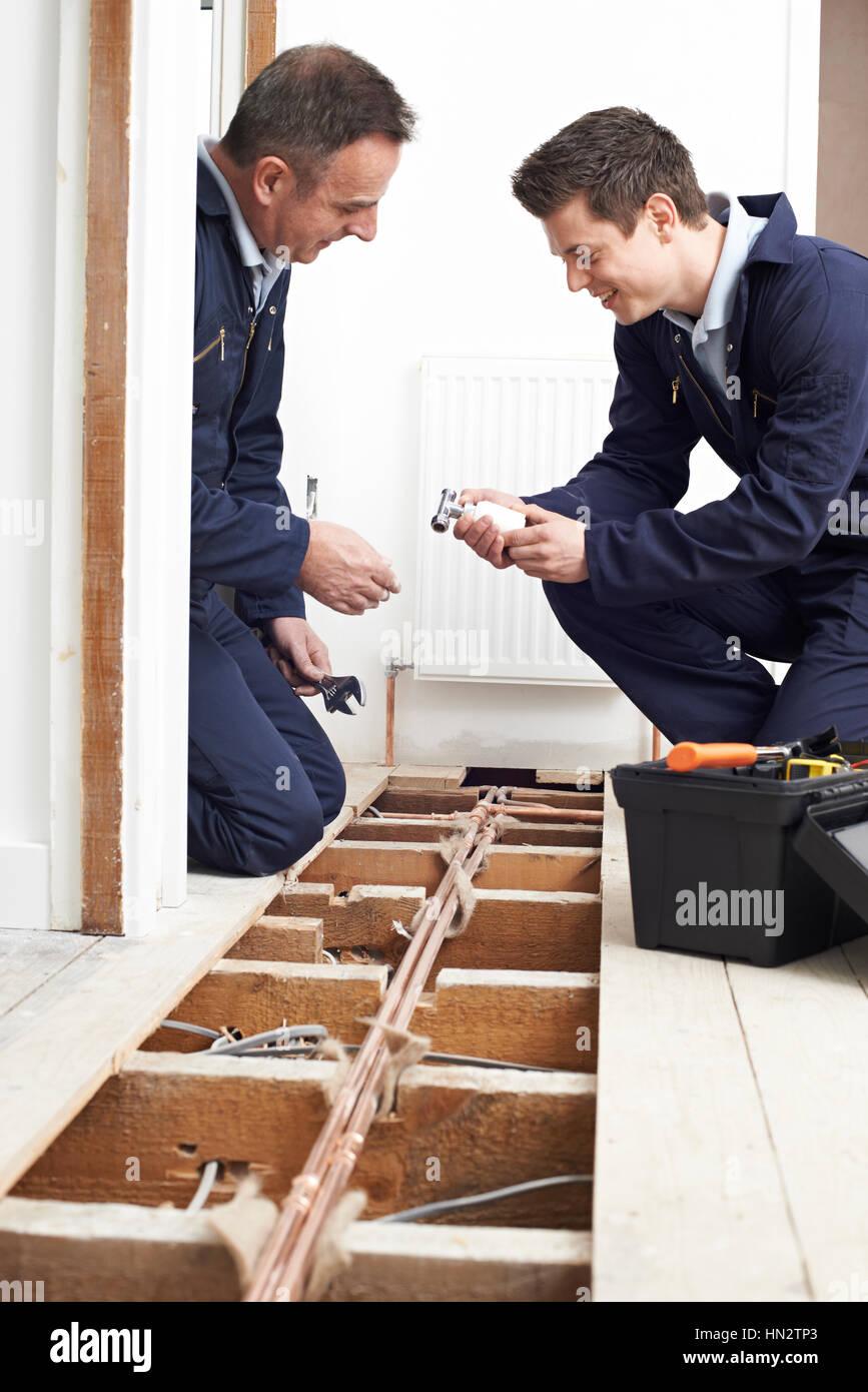Klempner und Lehrling Einbau Zentralheizung im Haus Stockbild