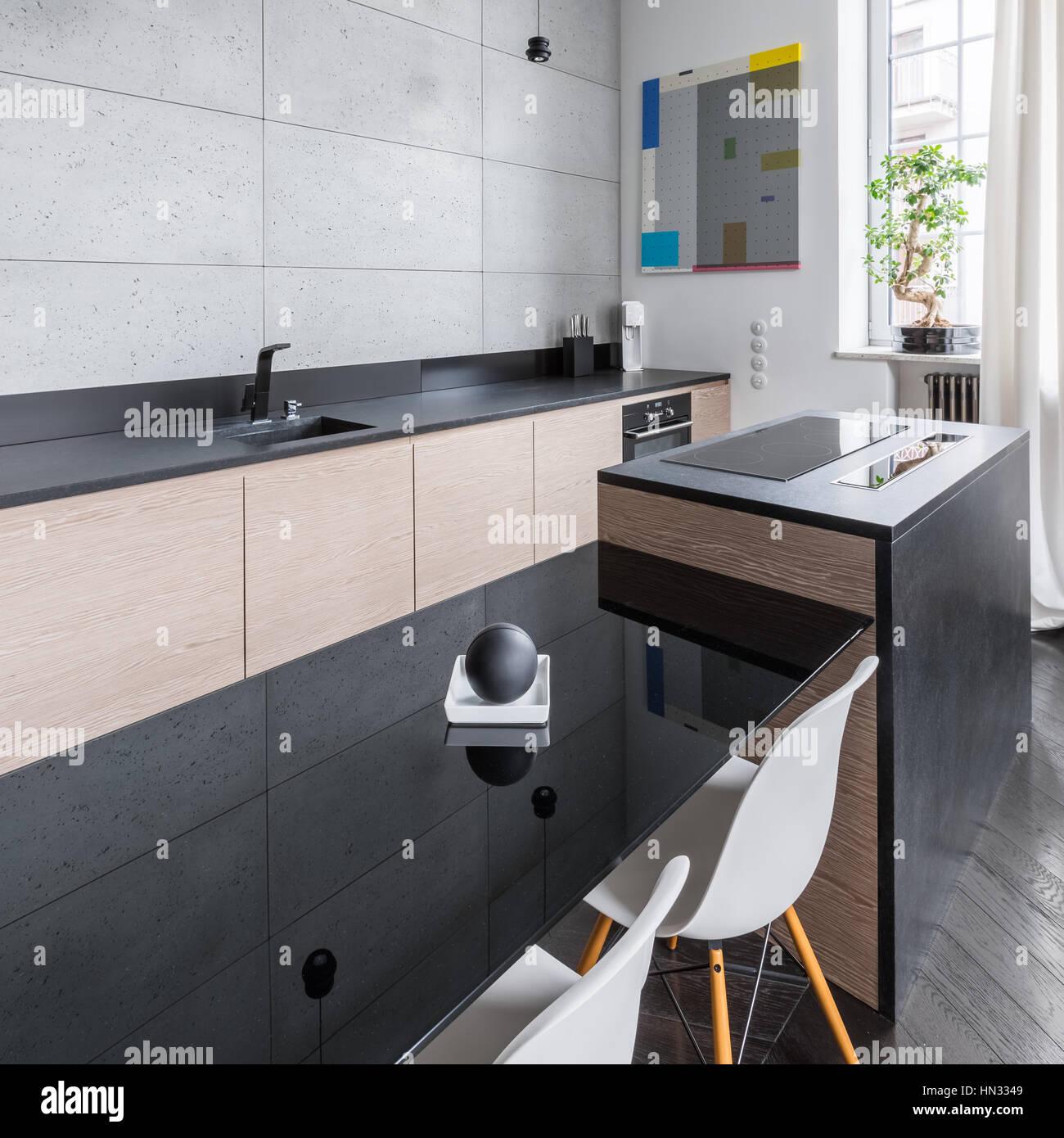 Moderne und elegante Küche mit schwarzen Arbeitsplatte und Tisch und ...