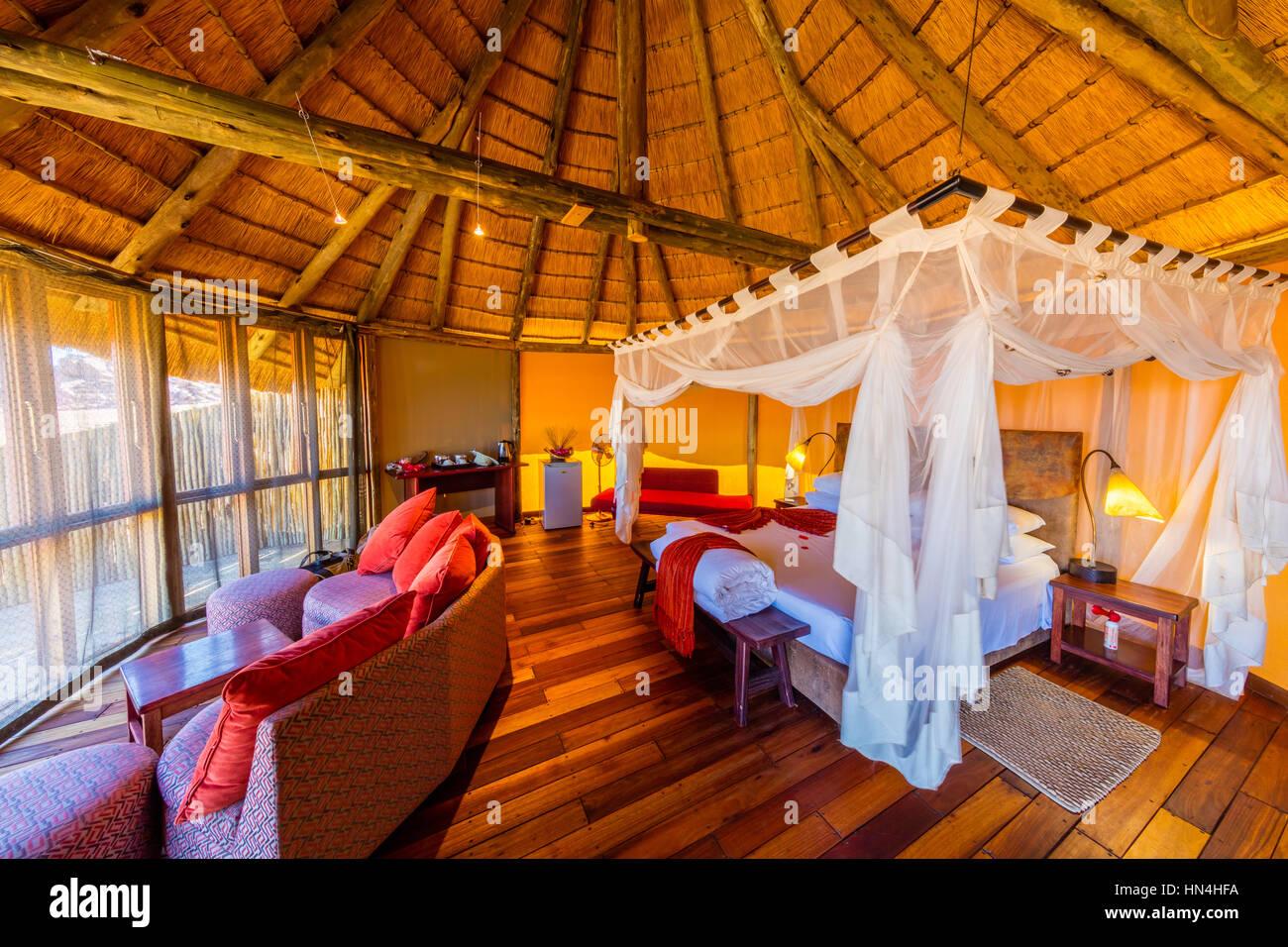 Sossus Dune Lodge liegt gegen die tief liegenden Berge im Namib-Naukluft-Nationalpark, die Gäste mit einer Stockbild