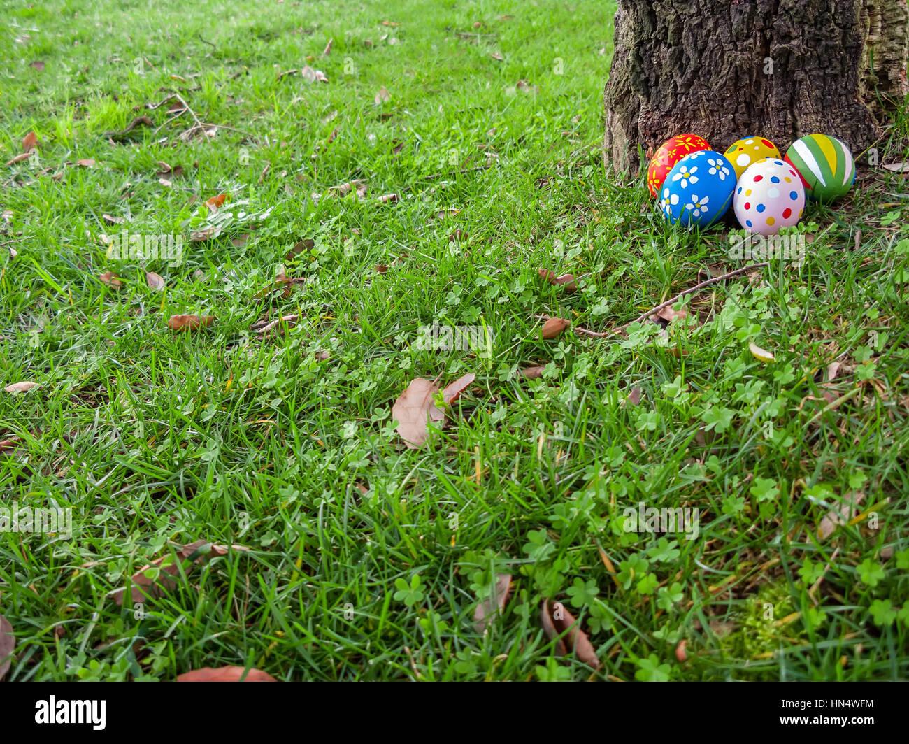 Ostereier versteckt hinter einem Baumstamm für die Jagd gemalt Spiel ...