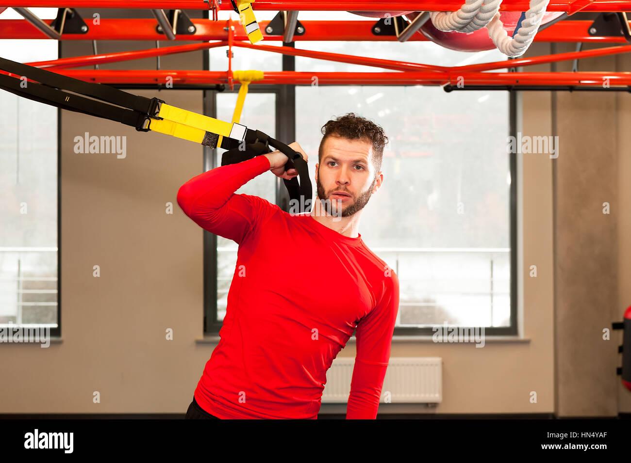TRX Training. CrossFit Lehrer in der Turnhalle TRX-Bewegung zu tun. Fitnesstraining Mann an den Ringen. Fitness Stockbild