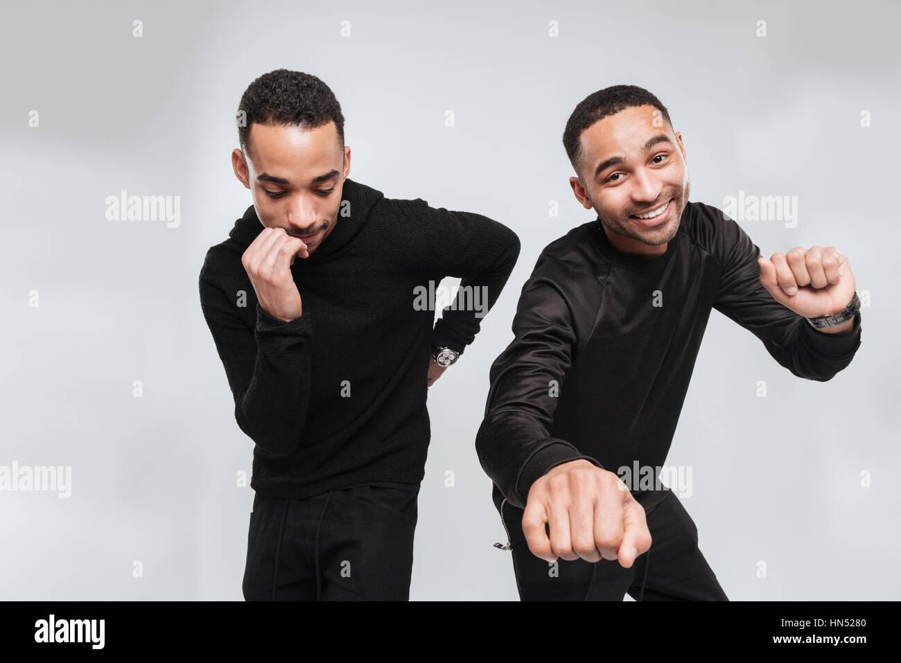 Bild von zwei Jungen glücklich afrikanische Männer tanzen über weißen Hintergrund beim Blick auf Kamera und beiseite. Stockfoto