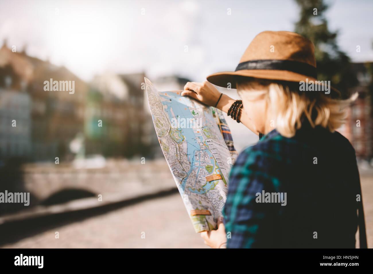 Seitenansicht der jungen Frau mit Hut, Blick auf einen Stadtplan. Touristen auf der Suche nach Navigationsroute Stockbild