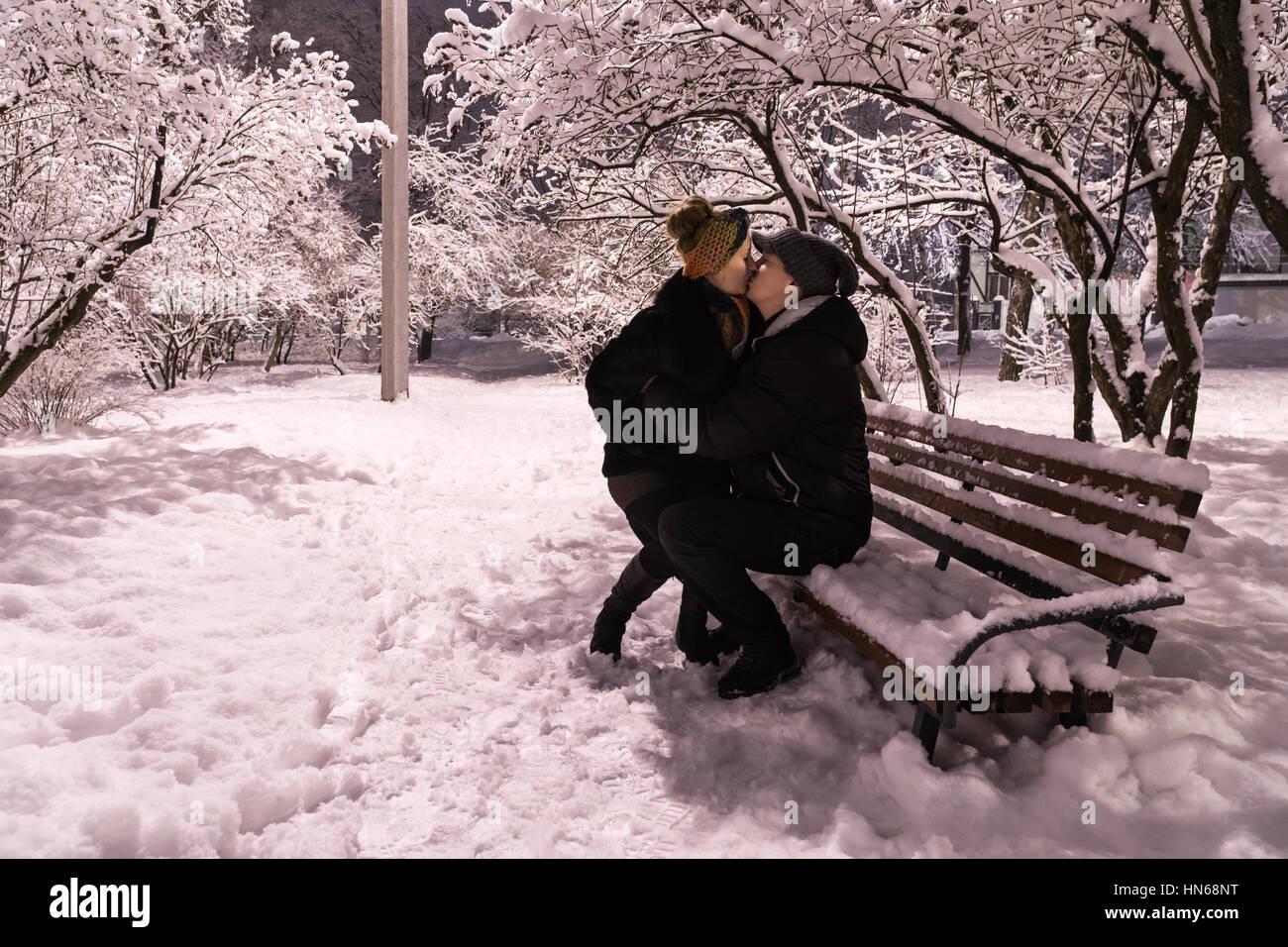 Im winter einer verschneiten nacht eine frau sitzt auf dem schoß
